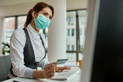 Businesswoman with face mask using computer and shopping on the internet with credit card in the office during COVID-19 pandemic.