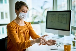 Businesswoman with face mask using hand sanitizer while cleaning her hands in the office.