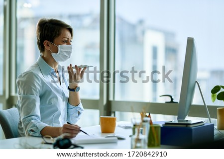 Businesswoman with face mask working on a computer while recording voice message on smart phone in the office.