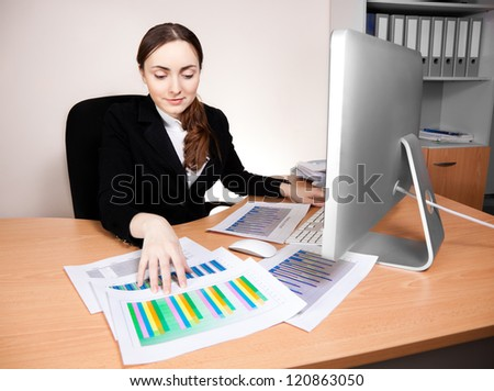 Businesswoman with financial report at office