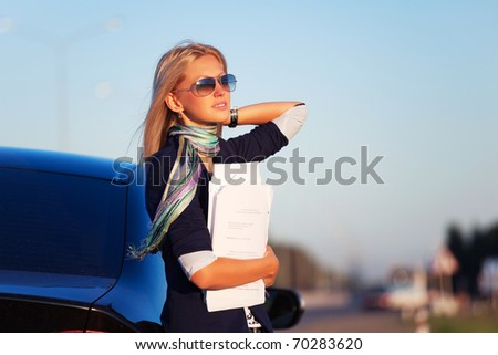 Businesswoman with financial reports against a highway