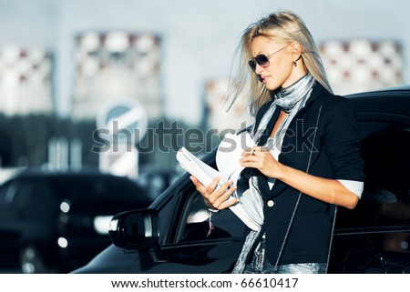 Businesswoman with financial reports against industrial background.