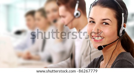 Businesswoman with headset smiling at  camera in call center. Businessmen in headsets on background