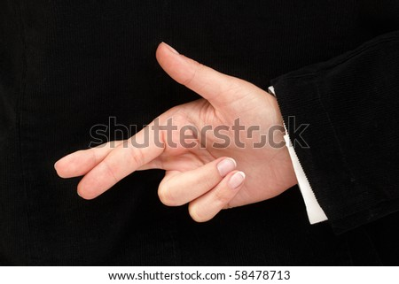 Businesswoman with her fingers crossed behind her back for good luck