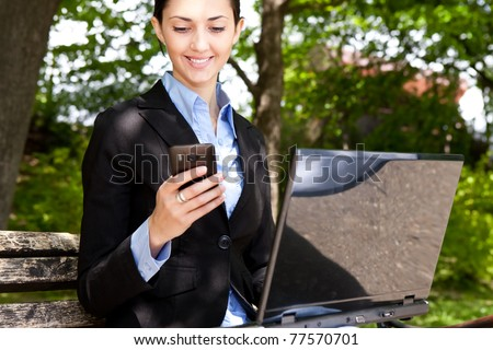 businesswoman with laptop and mobile phone in nature