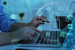 Businesswoman with laptop, desktop at office interior, blue glowing information protection icons. Padlock and business data symbols. Concept of cyber security and data storage