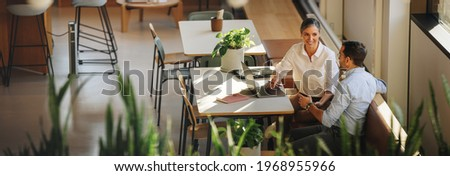 Businesswoman with laptop explaining project details to colleague at office desk. Business partners having meeting in coworking office space.