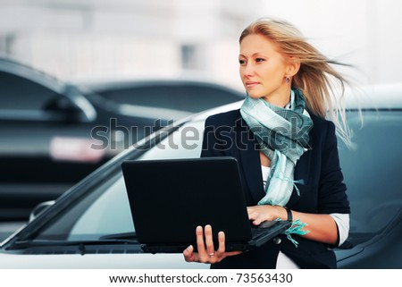 Businesswoman with laptop on a parking