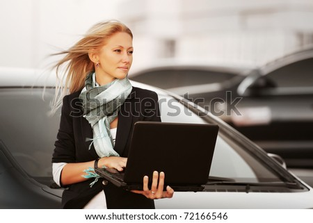 Businesswoman with laptop on the parking