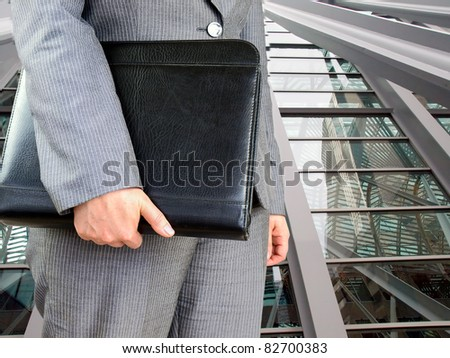 Businesswoman with leather folder ready for meeting.