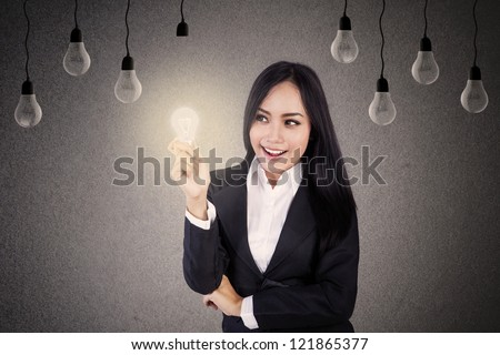 Businesswoman with lit light bulb and many light bulbs on the background