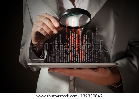 Businesswoman with magnifier glass examining binary code