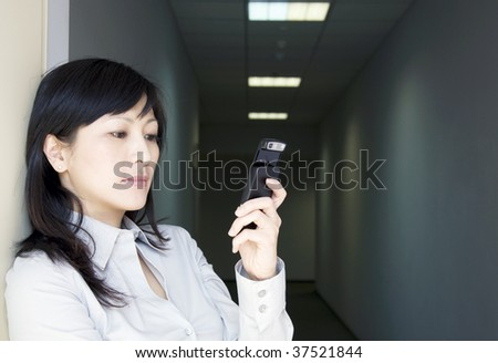 businesswoman with mobile phone in a dark corridor