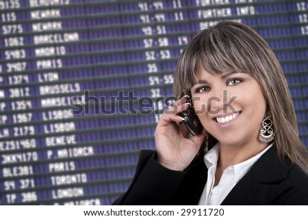 businesswoman with mobile phone in international airport - departure billboard in background