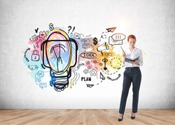 Businesswoman with notebook and pen in hands, light bulb with ideas and business strategy, plans and messages drawn on a concrete wall in office room with parquet. Concept of idea and plan