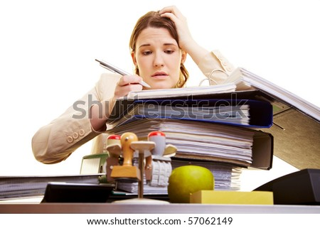 Businesswoman with pen reading in files on her desk