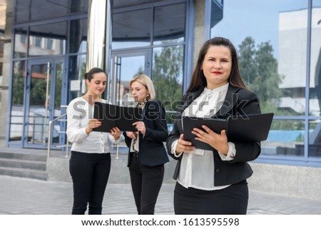 Businesswoman with tablet looking in camera. Her colleagues discussing information in folder