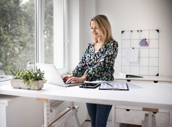 Businesswoman working at ergonomic standing workstation.