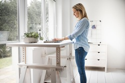 Businesswoman working at ergonomic standing workstation.