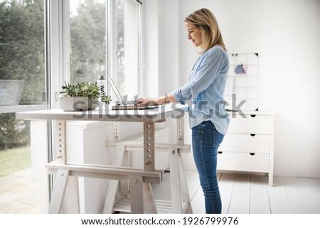 Businesswoman working at ergonomic standing workstation. Stockfoto ©