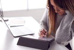 Businesswoman Working From Home Drawing On Digital Tablet Using Stylus Pen
