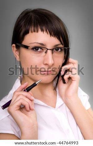 Businesswoman working, holding a cellphone.