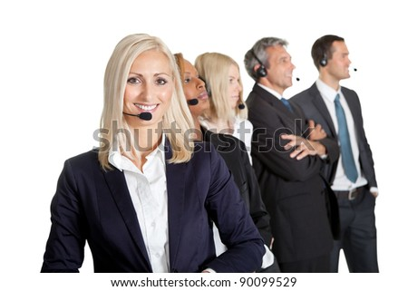 Businesswoman working in a call center with her team in background looking away