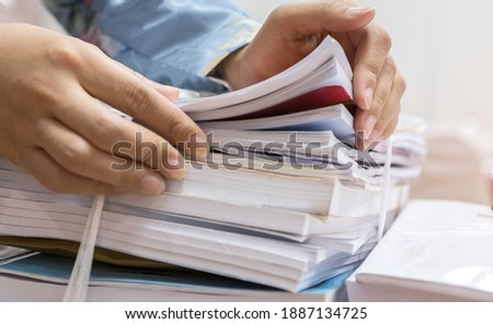 Businesswoman working in stacks of paperwork files for searching infomation unfinished documents about pile audit form on desk office and investigate financial doc in busy workload Stock foto ©