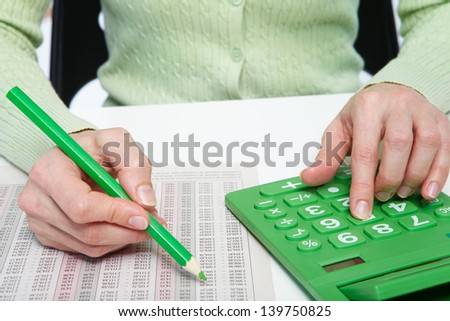 Businesswoman working in the office with calculator - stock photo