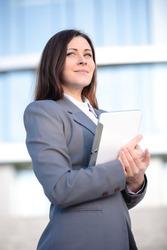 Businesswoman working on digital tablet outdoor over modern building background