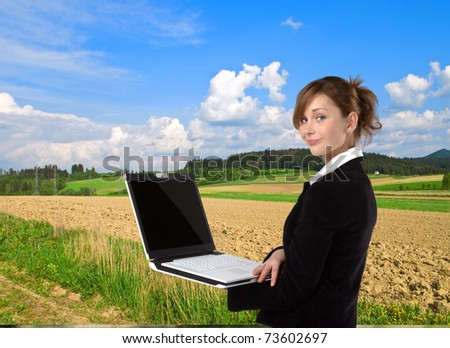 Businesswoman working on laptop computer, in nature