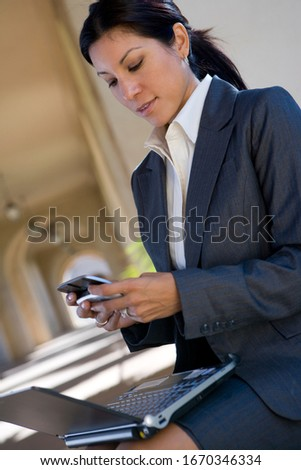Businesswoman working outdoors on laptop checking text messages