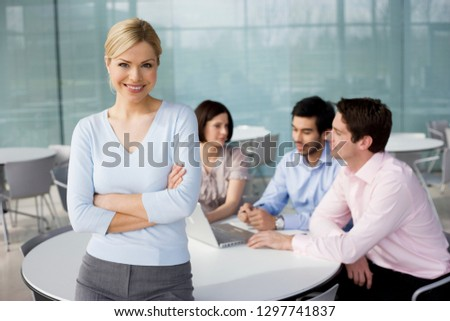 Businesswoman working with colleagues in team meeting smiling at camera