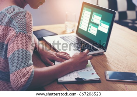 Businesswoman working with laptop, Writing something idea on notebook or check list in office