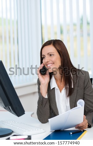 Businesswoman working with paperwork and a computer at her desk smiling and chatting on her mobile phone