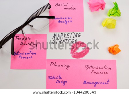 Businesswoman  workplace with lipstick stamp, glasses and handwritten marketing strategy plan #1044280543