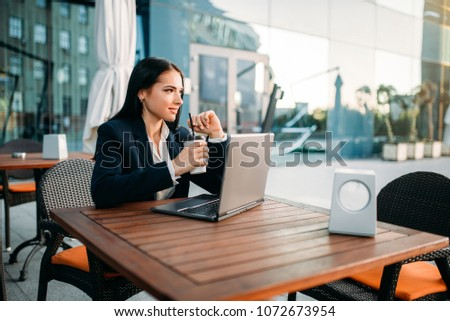 Businesswoman works on laptop in office, top view. Modern building, financial center, cityscape. Female businessperson in suit at workplace