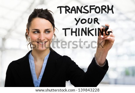 Businesswoman writing a motivational concept on the screen