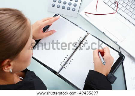 Businesswoman writing into notebook, overhead shot.