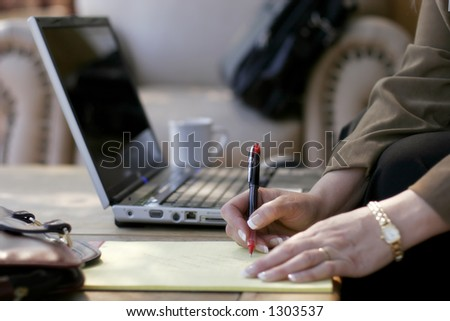 Businesswoman Writing Notes next to her Laptop Computer in a Hotel Atrium (shallow focus point on hand with pen).