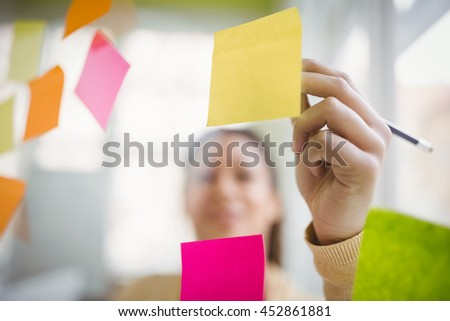 Businesswoman writing on adhesive notes in creative office #452861881