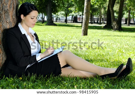 Businesswoman writing something to diary, sitting on green grass in park