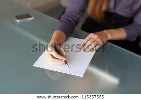 Businesswoman writing with pen on paper