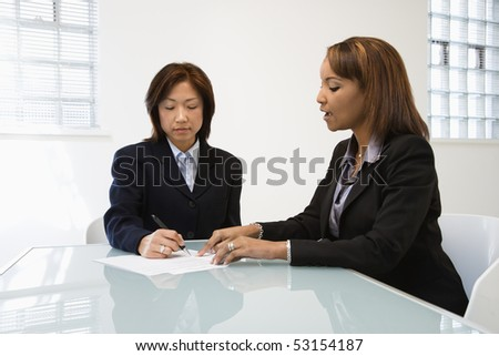 Businesswomen discussing paperwork at office desk.