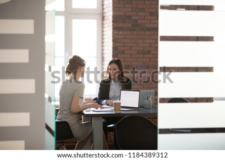 Businesswomen discussing project results and planning work in meeting room, female marketing or sales executives talking in office, serious women colleagues sharing ideas about new corporate strategy #1184389312