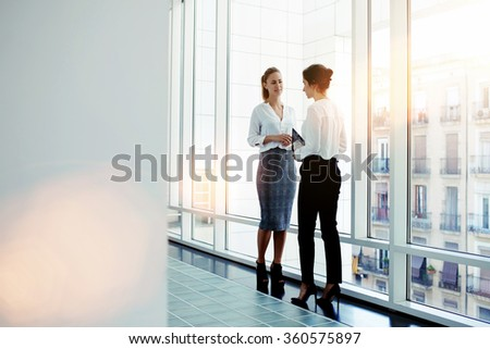 Businesswomen dressed in formal wear talking about work while meeting in hallway company, two female intelligent managers discussed plan the future conference while standing near big office window