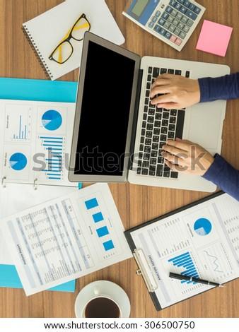 businesswomen hand working with digital laptop computer on wooden desk in office. top view
