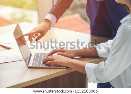 Businesswomen pointing at the laptop screen while her colleague/secretary is typing. #1152183986