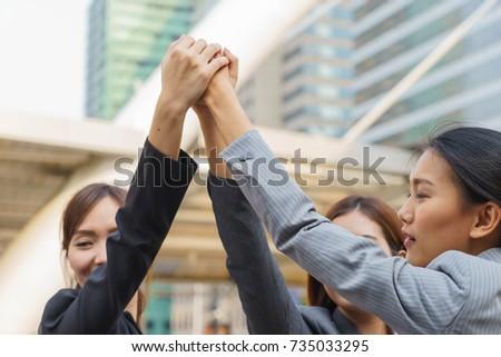 Businesswomen put hands together, collaboration concept. #735033295