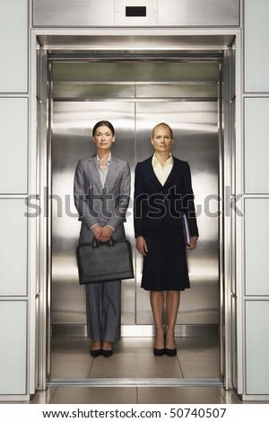 Businesswomen Side by Side in Elevator, portrait, front view